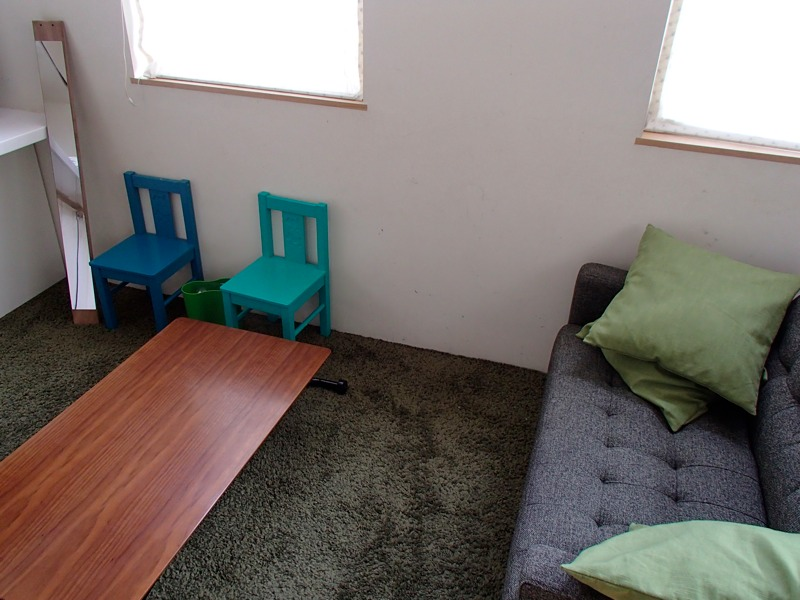 グリーンの椅子とゴミ箱とカーペットとソファとクッション